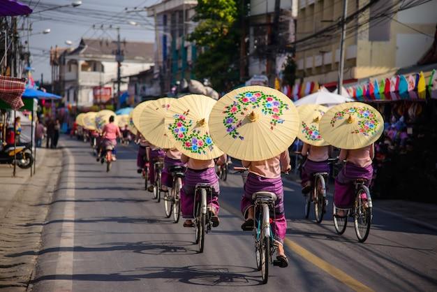 Bosang傘祭りチェンマイタイで美しい傘とサイクリングショーを開催している女性