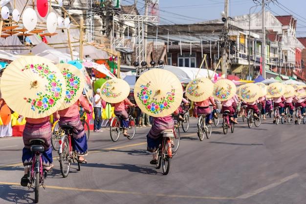 ボサン傘祭りチェンマイタイで美しい傘とサイクリングショーを開催している女性