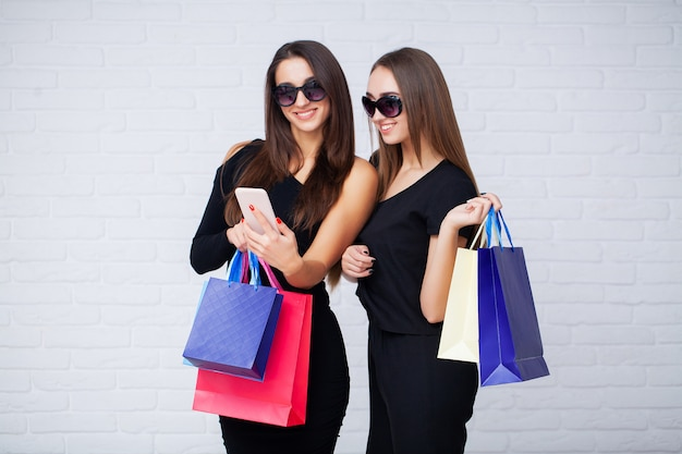Women holding black bags on light in black friday holiday