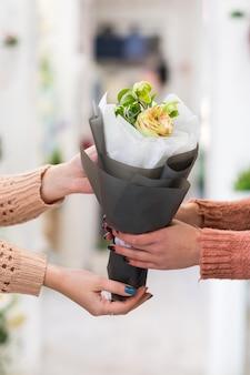 クラフト紙にバラとジャスミンの花束を持っている女性。フラワーアレンジメントの配達。
