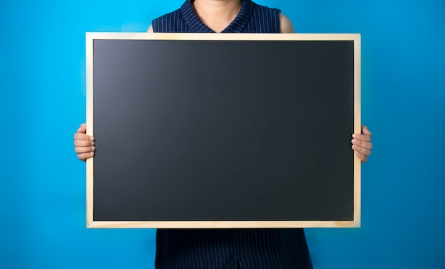 Women holding chalkboard against blue background