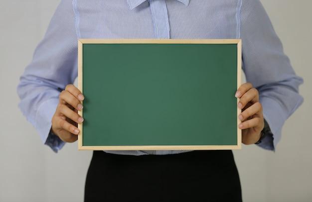 白い背景に対して黒板を保持している女性