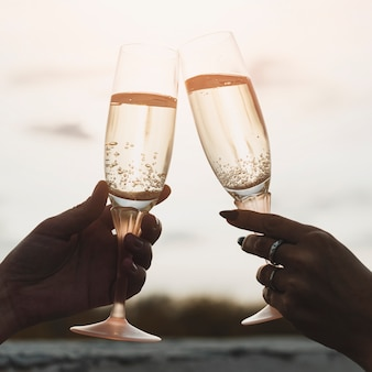 Women holding champagne  glasses on the background of sunset