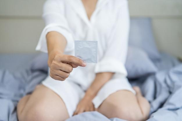 침실에서 침대에 앉아 콘돔을 들고 여성
