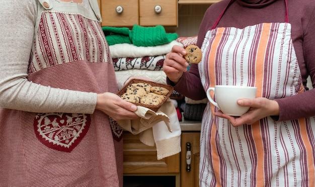 キッチンにたくさんの異なるプルオーバーが付いたお祝いのエプロンに身を包んだコーヒーとビスケットのカップを持っている女性。