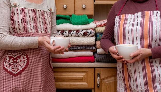 キッチンにたくさんの異なるプルオーバーが付いたお祝いのエプロンに身を包んだお茶やコーヒーを持っている女性。