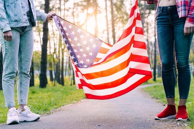 公園でアメリカの国旗を保持している女性