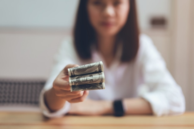 Women holding and give dollar money in the office. the concept of spending by cash.