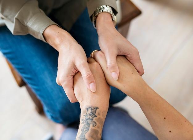 Women holding hands support