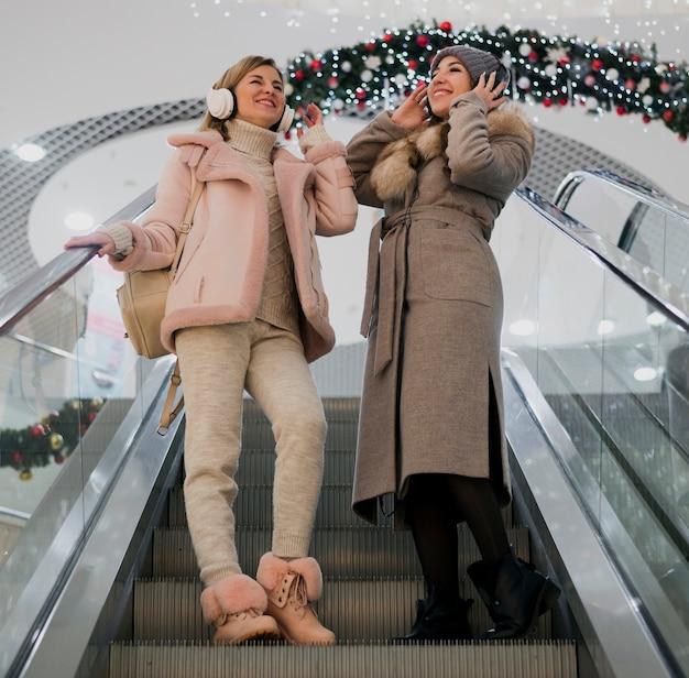Женщины держат на голове эшафоны на эскалаторе