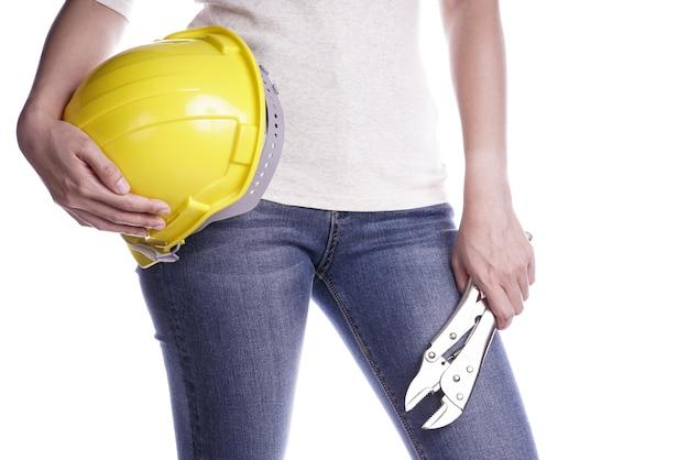 ヘルメットとレンチを手に持っている女性。職人ツール