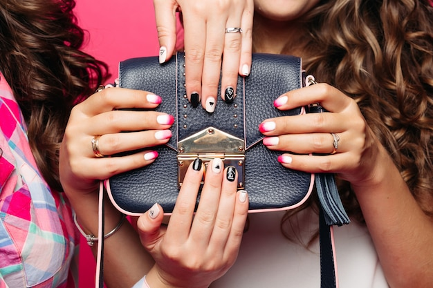 Women holding leather handbag with trendy manicure.