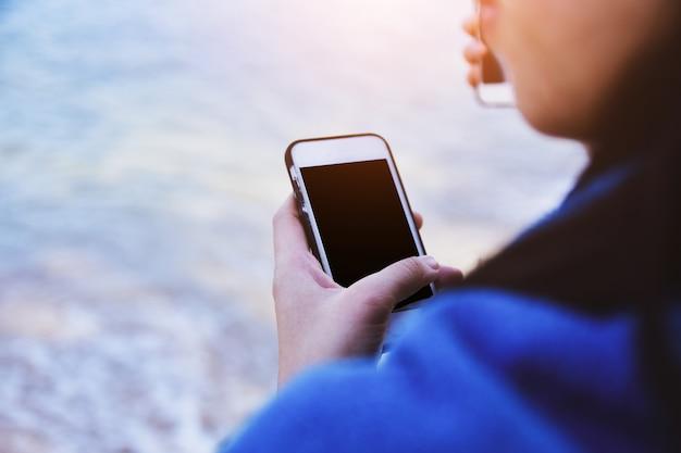 海でインターネットのオンライン技術を使用してモバイルのスマートフォンを保持している女性