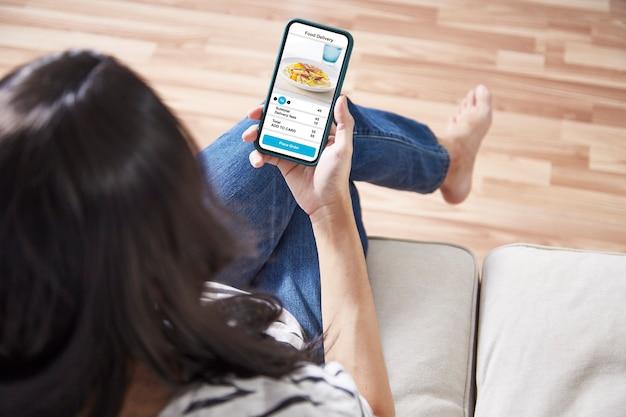 オンラインでアプリケーション配信食品と電話を保持している女性