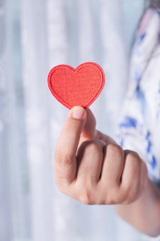 Women holding red heart in hands close up