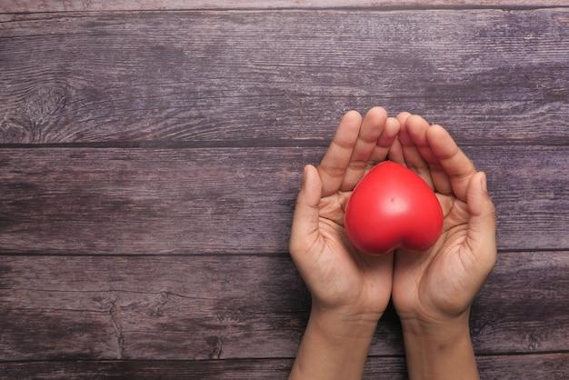 나무 테이블에 손에 붉은 마음을 잡고 여자.