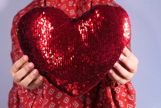 手で赤いハートを保持する女性