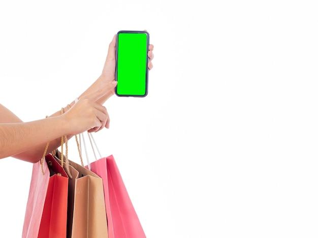 空白の画面と白い壁に買い物袋とスマートフォンを保持している女性