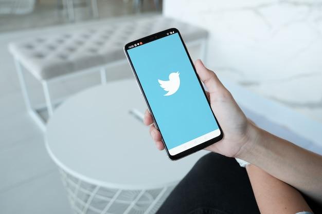 画面にtwitterロゴ付きのスマートフォンを保持している女性。 twitterは、マイクロブログとネットワーク通信のためのソーシャルメディアオンラインサービスです。