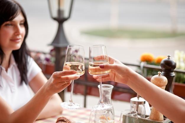 건배를 만드는 화이트 와인 잔을 들고 여성. 여자 건배.