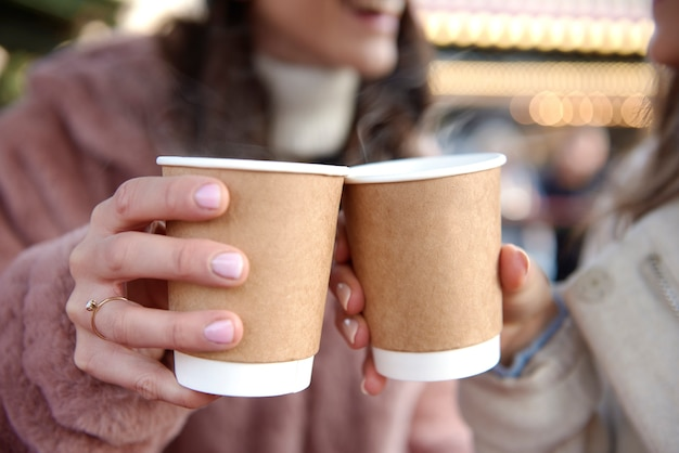 Women holding two cups with mulled wine