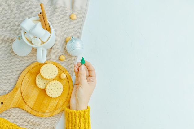 Women holds christmas toy in her hand cup of coffee with marshmallows and cinnamon cookies on a tray...