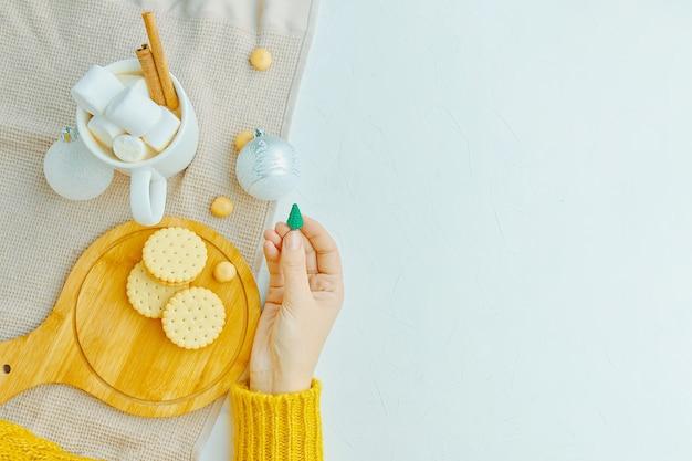 女性はトレイにマシュマロとシナモンクッキーを入れたコーヒーの手にクリスマスのおもちゃを持っています...