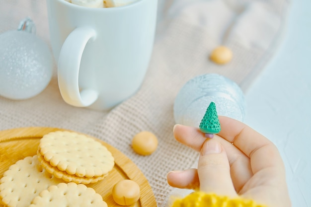 女性は彼女の手にクリスマスのおもちゃを持っています白いマグカップクッキーとキャンディーをトレイに、テーブルクロスを...