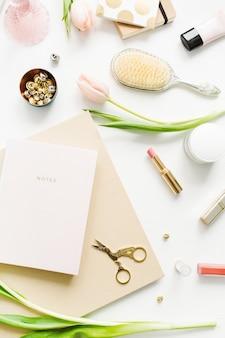 白い背景にピンクのチューリップの花、ノート、アクセサリー、化粧品を使った女性のホーム オフィス デスク。フラットレイ、トップ ビュー