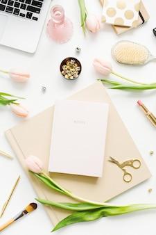 女性のホーム オフィス デスク。ノート パソコン、ピンクのチューリップの花、ノート、アクセサリー、化粧品を備えたワークスペース。フラットレイ、トップ ビュー