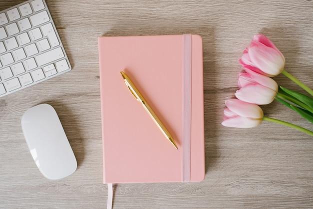 女性のホームオフィスデスク。ノートパソコン、ピンクのチューリップの花、ノートブックのあるワークスペース。フラットレイ、上面図。ファッションブログの構成。