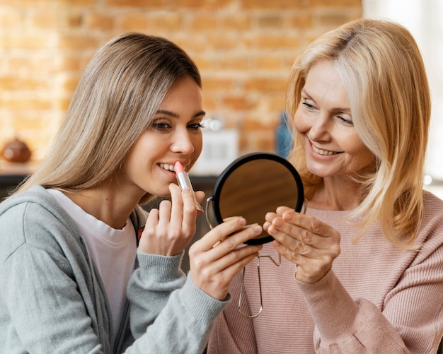 Women at home using lipstick together