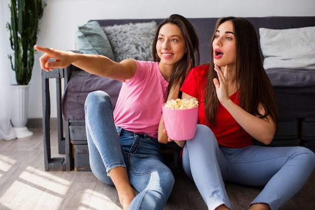 Women at home watching tv and eating popcorn