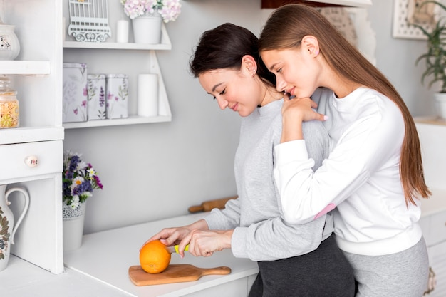 Women hugging each other while cutting orange