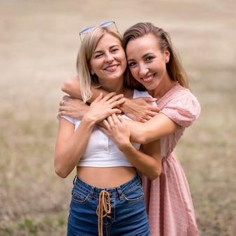 Женщины обнимают подругу сзади