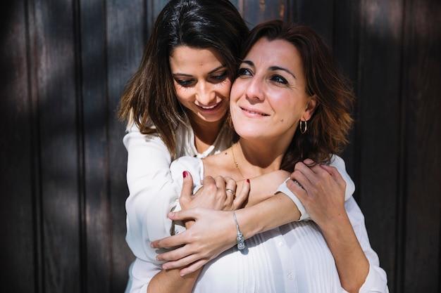 Women hugging near wooden door