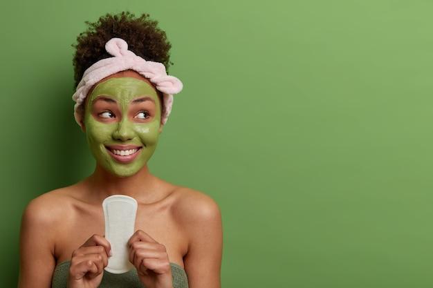女性、衛生、美容、美容のコンセプト。幸せな幸せな女性は、月経中に使用するためのきれいな生理用ナプキンを保持し、右側に歯を見せる笑顔で見え、緑の壁に隔離されています