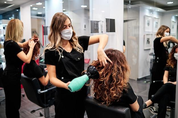 社会的距離と保護マスクを備えた美容院の女性
