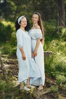 夏の森の女性。青いドレスを着た女性。家族のポーズと抱擁。