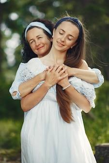 Женщины в летнем лесу. дама в голубом платье. семья позирует и обнимает.