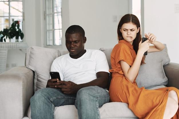 Женщины в сарафане смотрят на мужчину с мобильным телефоном на диване