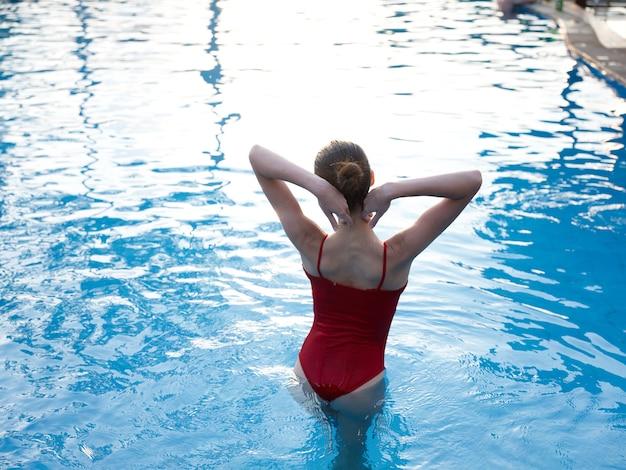 水着姿の女性がプールに入り、両手を頭の後ろに抱えて後ろ姿