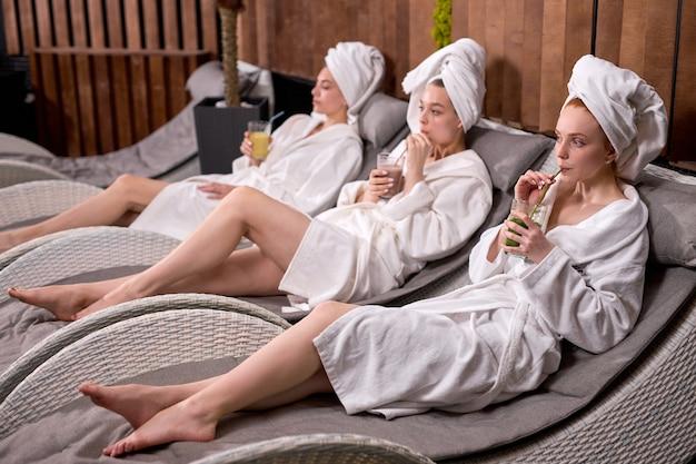 목욕 가운을 입은 여성들은 미용 시술 후 천연 유기농 주스를 즐기며 스파 리조트 호텔 살롱에서 시간을 보냅니다. 바디 케어, 웰빙 및 편안한 개념.