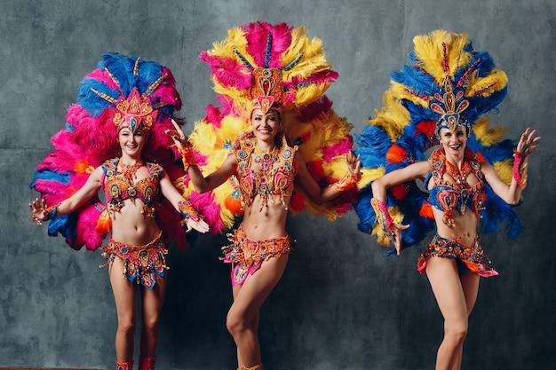 Женщины в карнавальном костюме бразильской самбы с разноцветным оперением из перьев