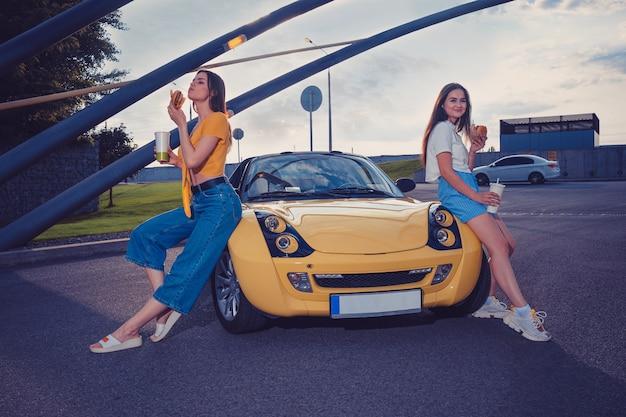 캐주얼 복장을 한 여성은 노란색 자동차의 후드에 앉아있는 동안 종이 컵에 음료를 들고 햄버거를 즐기고 있습니다.