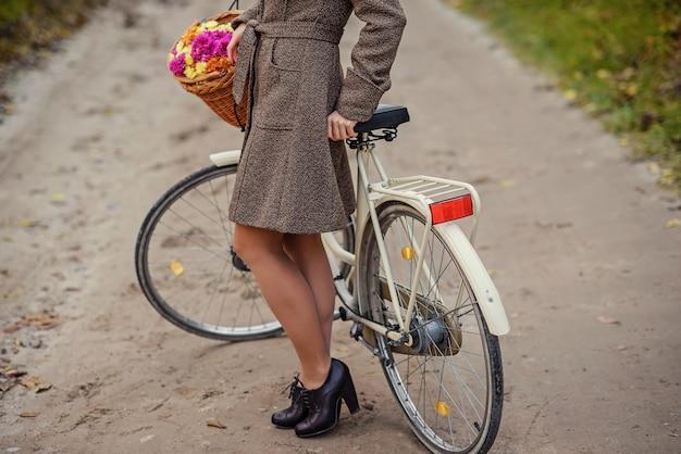 バスケットに花の花束を持つ女性の自転車の近くに立っている美しい女性の足のコートの女性。