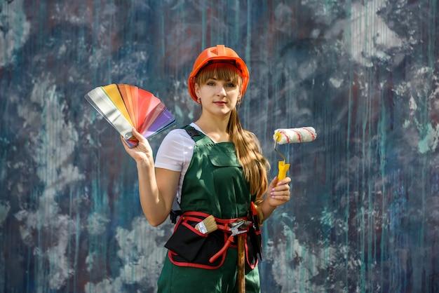 수리를위한 준비 색상 샘플러와 건설 의류 및 헬멧에 여성