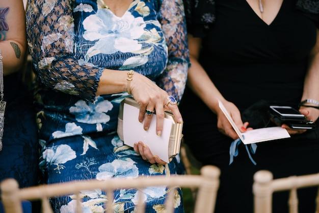 ドレスを着た女性は、リボンで飾られた招待状で芝生の椅子に座っています