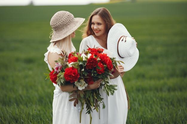 夏の畑に立っているエレガントなドレスの女性