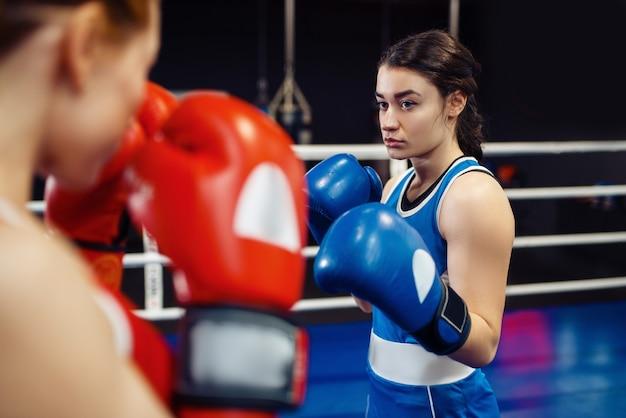 リングのボクシング、ボックストレーニングの手袋をはめた女性。ジムの女性ボクサー、スポーツクラブのキックボクシングスパーリングパートナー、パンチ練習